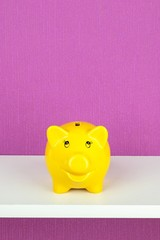 A happy yellow piggy bank on a shelf with copy space background