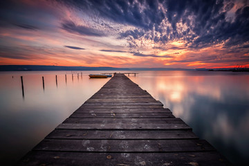 Foto op Plexiglas Grijs Magnificent lake sunset with boats and a wooden pier