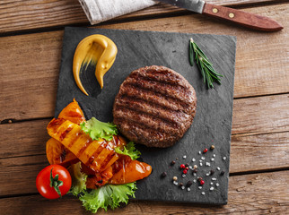 Fototapete - burger grill with vegetables and sauce on a wooden surface