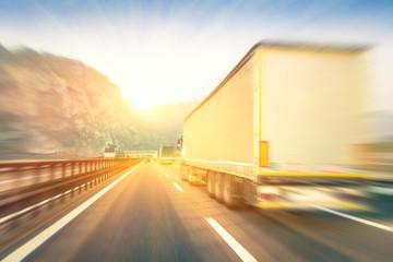 Semi trucks speeding on the highway at sunset