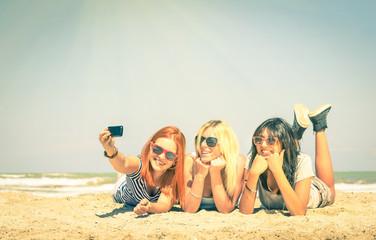 Happy girlfriends best friends taking a selfie at beach
