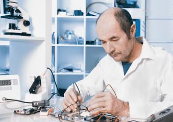 Senior male tech repairs circuit board, toned image