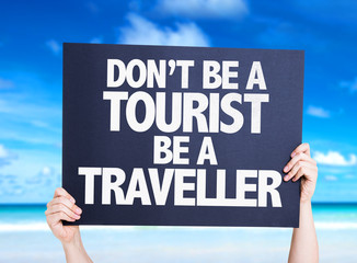Don't be a Tourist Be a Traveller card with beach background