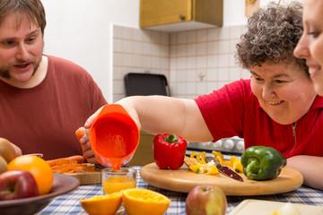 Geistig behinderte Frau mit Betreuern am Tisch mit viel Gemüse