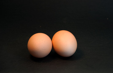 Two eggs on black background