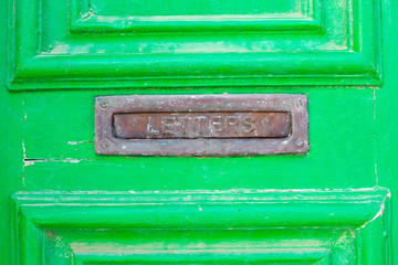 A letter box in a green old wooden door