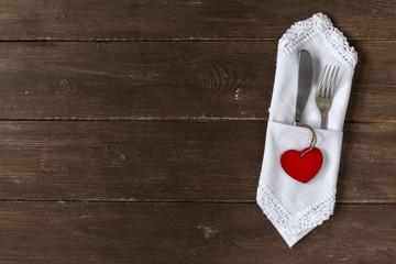 Besteck und Serviette auf Holzuntergrund mit Herzdeko