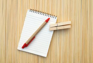 pen and notepad on bamboo matt