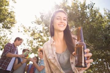 Happy friends in the park having beers