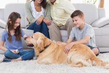 Siblings stroking dog while parents sitting on sofa