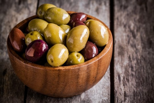 mixed olives in a wooden bowl closeup on a rustic table
