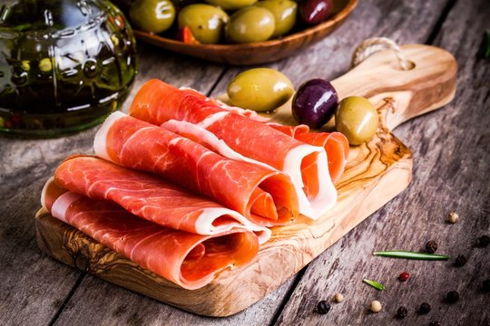 thin slices of prosciutto with mixed olives on a cutting board