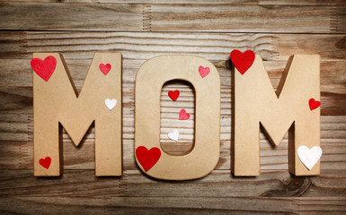 MOM text in big cardboard letters with heart shaped decorations