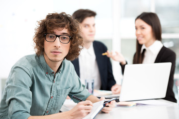 Young businessman using notebook with his business team on