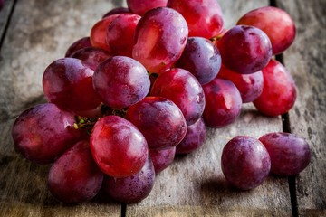 branch of ripe organic grapes on wooden background