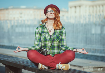 Hipster redhead woman in hat and glasses doing yoga on the bench