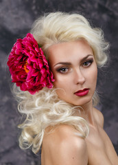 Beauty portrait of a blonde with a big red flower in hair
