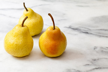 Yellow pears on white marble kitchen counter
