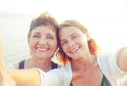 mother and adult daughter are doing Selfe on the beach