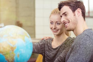modernes paar schaut auf einen globus