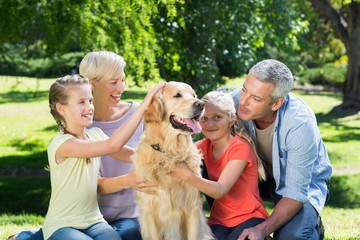 Happy family petting their dog in the park