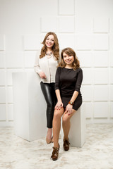 Two beautiful models posing in studio against white wall