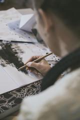 Looking over the shoulder of illustrator sketching