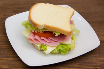 Slices of bread with ham and salad on wooden table