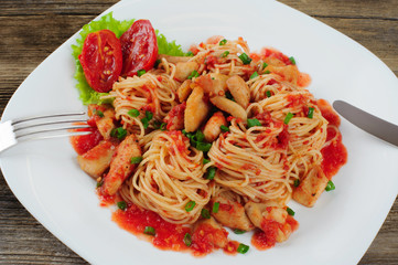 Pasta. Spaghetti with sauce and chicken on a plate.