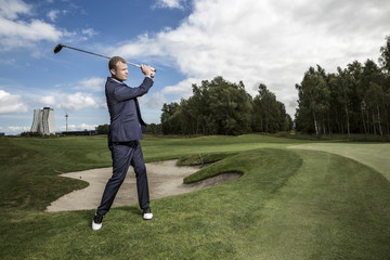 Businessman playing golf outdoors