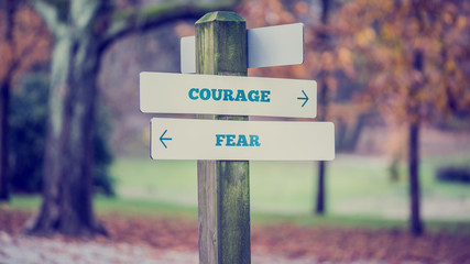 Rustic wooden sign in an autumn park with the words Courage - Fe Wall mural
