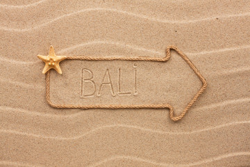 Arrow made of rope and sea shells with the word Bali on the sand