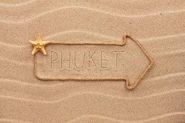 Arrow made of rope and sea shells with the word Phuket on the sa