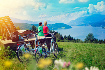 girls with e-bikes enjoying view to a lake-sportive holidays 04