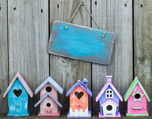 Blank blue sign hanging over colorful birdhouses