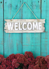 Welcome sign hanging on fence with flower border