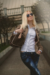 Beautiful blonde woman in sunglasses wearing loose dress in city
