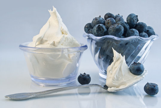 Delicious bowls of ripe blueberries and whipped cream