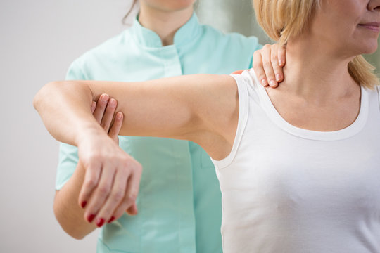 Physical therapist diagnosing patient