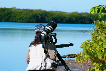 Professional female nature photographer with zoom lens