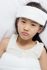 Little Asian child has fever and laying on the bed