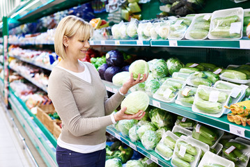 Woman buys white cabbage in store