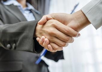 Low angle of businesswomen handshaking
