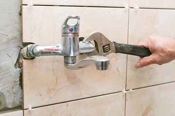 Water fixing - plumber hands with wratch fix tap