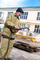 Industrial man worker foment blow torch burner
