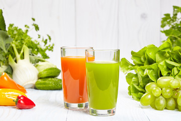 Glasses with fresh vegetable juices isolated on white table. Det