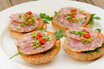 Ham sandwiches with chili, parsley and scallion on white plate c