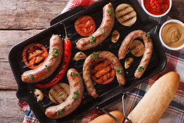 sausages with vegetables on a grill closeup. horizontal top view