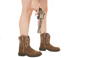 Horizontal woman's legs in boots with a gun