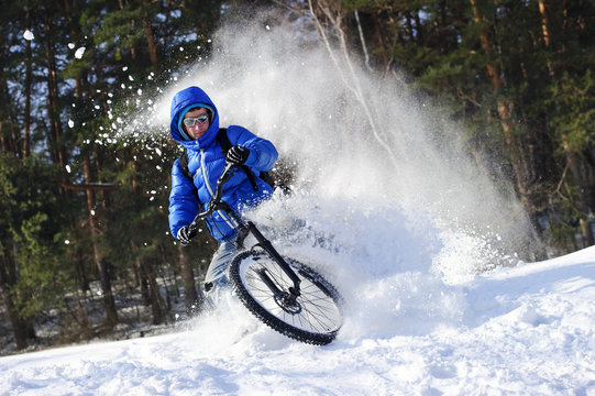 Extreme cycling - rider on mountain bike in snow winter